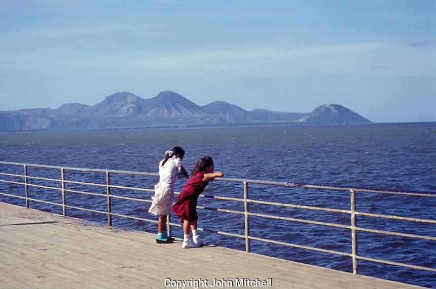 Two Nicaraguan girls enjoying the view of Lake Xolotlan from the Malecon promenade in  Managua, Nicaragua