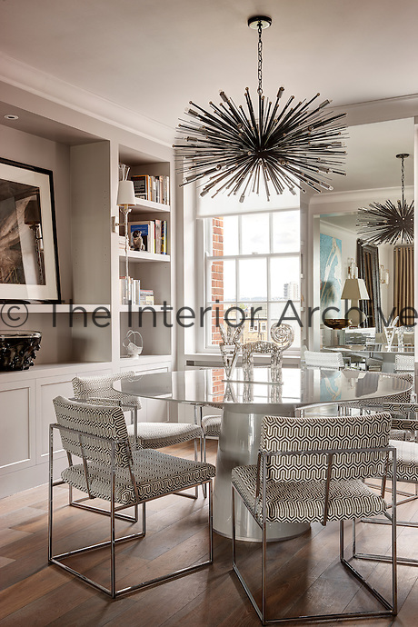 A light dining room with a built-in display unit filling one wall. A spiky pendant light hangs above a glass topped dining table surrounded by six metal dining chairs upholstered in an abstract monochrome patterned fabric.