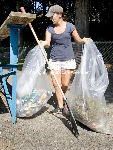 THOMASTON CT. 25 August 2013-082513SV04-Tricia Brody of Thomaston bags trash around the bleaches at Reeve's Field in Thomaston Sunday. Volunteers turned out to clean the park after organizing on the town&rsquo;s facebook page.<br /> Steven Valenti Republican-American