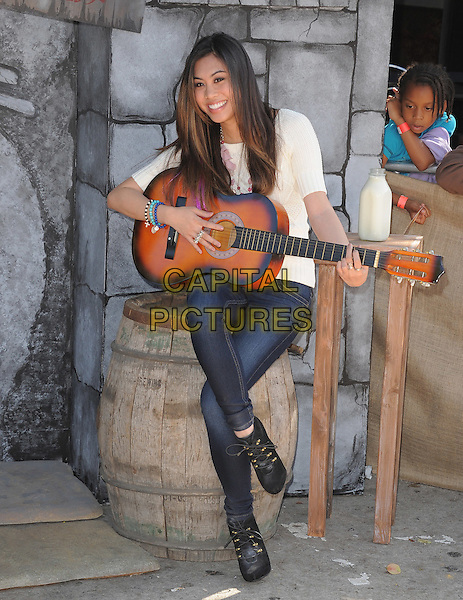 Ashley Argota.The L.A. Premiere of 'Puss in Boots' held at The Regency Village  Theatre in Westwood, California, USA..October 23rd, 2011 .full length white top sitting jeans denim barrel guitar legs crossed.CAP/RKE/DVS.©DVS/RockinExposures/Capital Pictures.