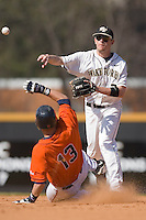 Dustin Hood #21 of the Wake Forest Demon Deacons turns a double play as Jared King #13 of the Virginia Cavaliers slides into second base at Wake Forest Baseball Park March 8, 2009 in Winston-Salem, NC. (Photo by Brian Westerholt / Four Seam Images)