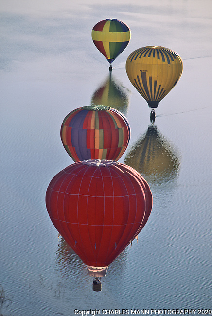 Colorful balloons touch down on the water at a local lake during the Farmington Balloon Festival in Farmington, NM