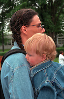 American Indian dad holding son age 30 and 2 at Vietnam Wall on Memorial Day . St Paul Minnesota USA