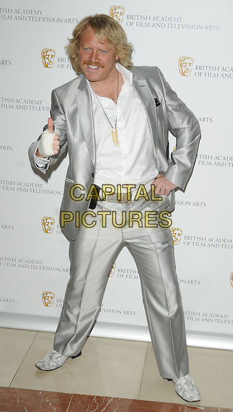 LEIGH FRANCIS aka KEITH LEMON, AVID MERRION.British Academy Television Craft Awards at the Hilton, Park Lane, London, England. .May 23rd 2010 .BAFTA full length silver shiny suit white shirt belt smiling hand on hip thumb up bandage injury wound.CAP/CAN.©Can Nguyen/Capital Pictures.