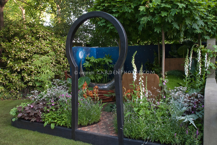 Creating an outdoor room with the simple use of a Moon gate, painted garden wall with night sky and stars, perennials, flowers, trees