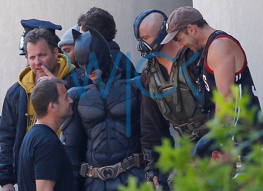 Christian Bale, playing Batman, talks with Tom Hardy, playing Bane, and crew members in between scenes during the filming of the new Batman: Dark Knight Rises movie at the Mellon Institute building in the Oakland neighborhood of Pittsburgh, PA on July 31, 2011.