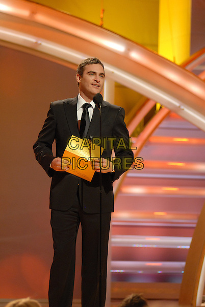 "JOAQUIN PHOENIX.Presents the award for Best Performance By An Actress In A Motion Picture Musical or Comedy.Telecast - 64th Annual Golden Globe Awards, Beverly Hills HIlton, Beverly Hills, California, USA..January 15th 2007. .globes full length microphone black suit stage.CAP/AW.Please use accompanying story.Supplied by Capital Pictures.© HFPA"" and ""64th Golden Globe Awards"""