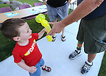 Volunteer Kurt, right, makes a balloon dog for Brian Kelley, 3, during the Journey of Hope event at Western Nevada College in Carson City, Nev., on Friday, June 12, 2015. Nearly 30 cyclist rode into town Friday as part of the Pi Kappa Phi fraternity&rsquo;s cross-country ride to bring awareness and support to people with disabilities.<br /> Photo by Cathleen Allison/Nevada Photo Source