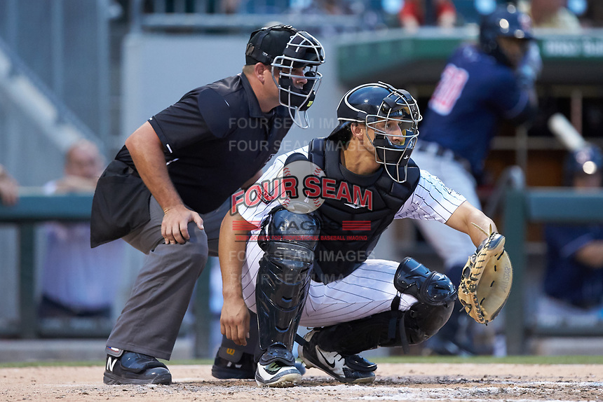 Charlotte Knights catcher Seby Zavala (23) sets a target as home plate umpire Jeremy Riggs looks on during the game against the Toledo Mud Hens at BB&T BallPark on June 22, 2018 in Charlotte, North Carolina. The Mud Hens defeated the Knights 4-0.  (Brian Westerholt/Four Seam Images)