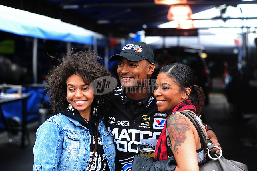 Nov. 10, 2011; Pomona, CA, USA; NHRA top fuel dragster driver Antron Brown (center) poses for a photo with fans during qualifying at the Auto Club Finals at Auto Club Raceway at Pomona. Mandatory Credit: Mark J. Rebilas-.