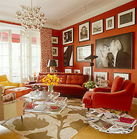 In the living room the sofa and club chairs are Patrick Naggar designs and the deep red walls and warm red and yellow upholstery create a cosy and welcoming feel