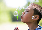 Leo, a 12-year-old orphan child from China, blows bubbles in Cottage Grove, Wis., during summer on June 17, 2016. Courtney and Donnie Henry are hosting the boy for a month as they advocate and strive to connect Leo with a forever family in the U.S. to adopt him. (Photo by Jeff Miller, www.jeffmillerphotography.com)