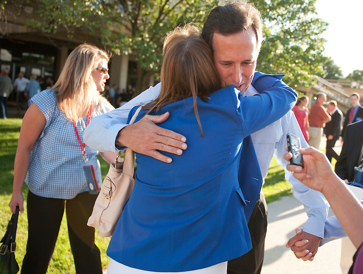 UNITED STATES - AUGUST 11:  Former Senator Rick Santorum, hugs a debate goers outside of Stephens Auditorium at Iowa State University before the Republican presidential debate in Ames, Iowa.  The debate will feature eight republican candidates including Santorum.   (Photo By Tom Williams/Roll Call)