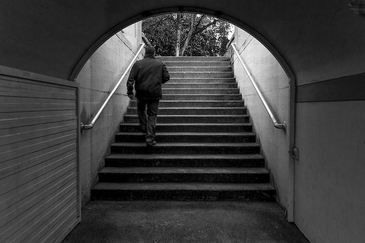 Man walking through dark passge and up a flight of stairs.