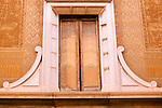 Window and faded frescos of a building in Como, Italy.