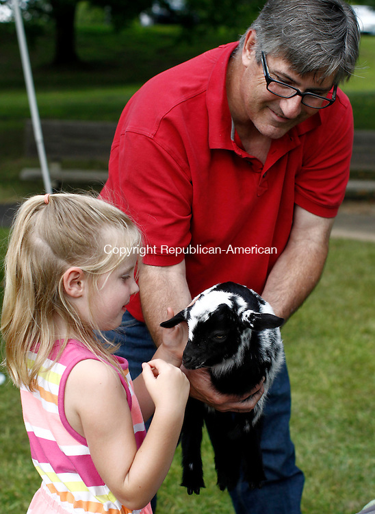 Southbury, CT- 31 July 2014-073114CM04-  Rick Agee, from Goatboy Soaps of New Milford, holds Shelly, a 3 week old Nigerian Dwarf goat as Madison Tate 5, of Southbury gives her a pet at the Town of Southbury's Farmer's Market in Southbury on Thursday. The market runs through the summer on every Thursday at the Southbury Town Hall.    Christopher Massa Republican-American