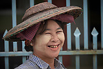 A woman smiles in Kalay, a town in Myanmar. The woman is wearing thanaka, a cosmetic paste, on her face.