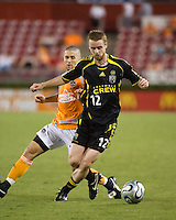 Columbus Crew midfielder Eddie Gaven (12) attempts to dribble past Houston Dynamo defender Wade Barrett (24). The Houston Dynamo tied the Columbus Crew 1-1 in a regular season MLS match at Robertson Stadium in Houston, TX on August 25, 2007.