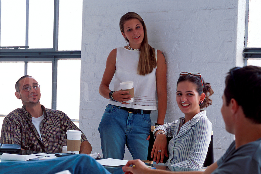 Young adults talk, drink coffee and work together as they hold a business meeting in a casual office setting.