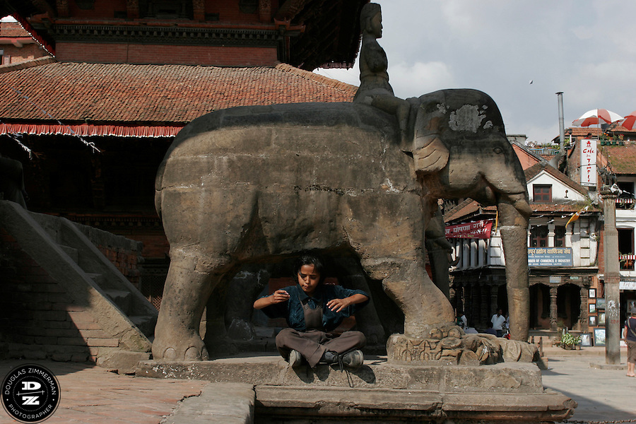 A young boy sits below a statue of an elephant among the temples and monuments of Patan's Durbar Square in Patan, Nepal.  Photograph by Douglas ZImmerman