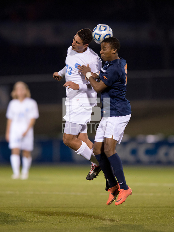 Raby George (33) of North Carolina goes up for a header with Marcus Salandy-Defour (16) of Virginia during the game at the Maryland SoccerPlex in Germantown, MD. North Carolina defeated Virginia on penalty kicks after playing to a 0-0 tie in regulation time.  With the win the Tarheels advanced to the finals of the ACC men's soccer tournament.