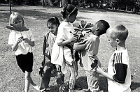 Primary schoolchildren collecting leaves in the park, Nottingham UK 1992