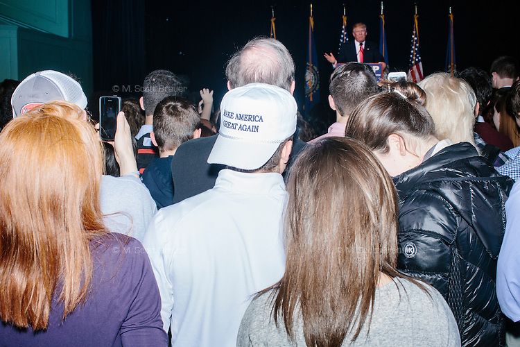 """A person wears a hat reading """"Make America Great Again"""" in the audience as real estate mogul and Republican presidential candidate Donald Trump speaks at a rally at Exeter Town Hall in Exeter, New Hampshire, on Thurs., Feb. 4, 2016."""