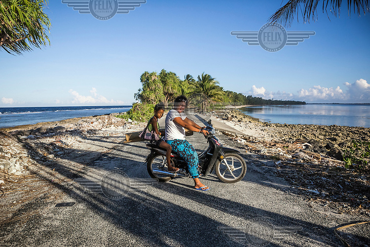 Patricia, 30, and her 10 year old daughter Serina on their scooter on the causeway at the narrowest part of the Funafuti Atoll. According to Patricia: 'When the 'King Tide' comes, this road gets completely flooded and people that live on the other side are cut off from the rest of the atoll until the water goes back and road workers clean the road of rocks.'