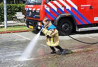 Nederland Westzaan. 2016. De Brandweer staat klaar om de deelnemers aan de jaarlijkse Prutrace schoon te spuiten. Jongentje oefent voor brandweerman. Foto Berlinda van Dam / Hollandse Hoogte
