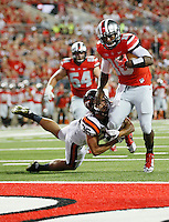 Ohio State Buckeyes quarterback J.T. Barrett (16) runs for a touchdown with Virginia Tech Hokies linebacker Chase Williams (36) tangling him up in the first quarter of the college football game between the Ohio State Buckeyes and the Virginia Tech Hokies at Ohio Stadium in Columbus, Saturday afternoon, September 6, 2014. (The Columbus Dispatch / Eamon Queeney)