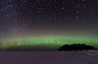 The colorful auroras stretching across the sky and a frozen Lake Superior shore. Little Presque Isle - Marquette, MI