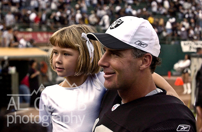 Oakland Raiders quarterback Rich Gannon (12) with young daughter after game on Sunday, September 29, 2002, in Oakland, California. The Raiders defeated the Titans 52-25.