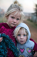 KRUGERSDORP, SOUTH AFRICA - JULY 18: Poor white Afrikaner children try to stay warm during a cold day outside their family shack in Munsieville township on July 18, 2018 in Krugersdorp a suburb in Johannesburg, South Africa. This black township, where South Africans and African immigrants live, now also has a separate section of poor white Afrikaners. They live side my side but they don't mix unless they have too. Many of the residents survive by begging at traffic lights and doing odd jobs. (Photo by Per-Anders Pettersson/Getty Images)