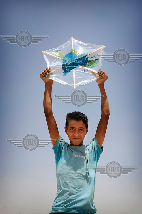 Syrian refugee Zakaria holds up his kite which he made himself and has his personal message of peace for his country written on it. 'My country is my home, here I'll always be a refugee' said Zakaria who fled Syria five months ago with his parents and siblings. On his kite he drew a big blue heart and said 'it is the love I have for my home.' /Felix Features