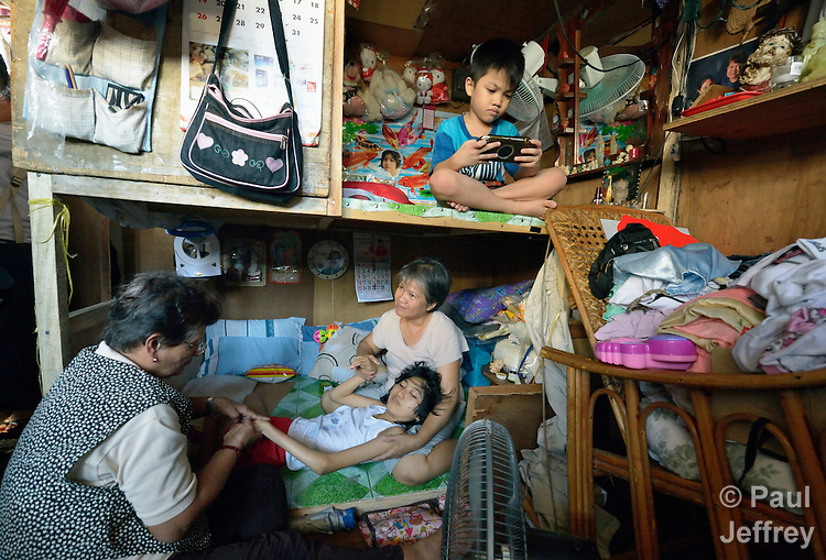Rafaela Valencia exercises the legs of Susan Dison's 15-year old daughter Susein, as Dison's 7-year old son Apo plays an electronic game in their crowded home in the Malate neighborhood of Manila. They are members of Kaisahan ng Magulang at Anak na Maykapansanan (Kaisaka), a mothers' group that carries out community based rehabilitation with families which have members with disabilities. Susein has cerebral palsy.