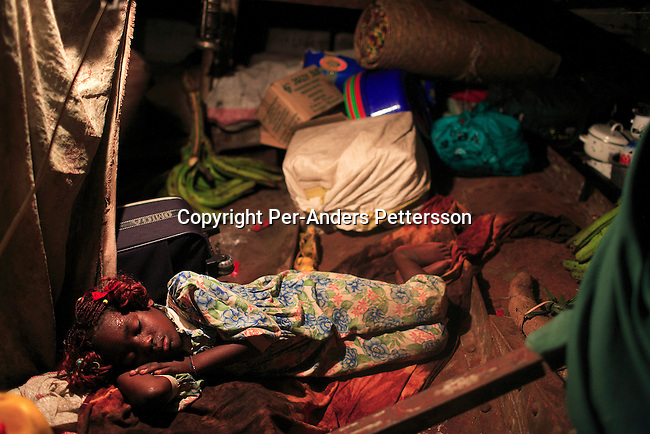 LUKUTU, DEMOCRATIC REPUBLIC OF CONGO MARCH 13: Noella Ndomte, age 8, sleeps under deck on a boat traveling on the Congo River from Kisangani to Kinshasa, the capital on March 13, 2006 in Lukutu, Congo, DRC. The Congo River is a lifeline for millions of people, who depend on it for transport and trade. The journey from Kisangani to Kinshasa is about 1750 kilometers, and it takes from 3-7 weeks on the river, depending on the boat. During the Mobuto era, big boats run by the state company ONATRA dominated the traffic on the river. These boats had cabins and restaurants etc. All the boats are now private and are mainly barges that transport goods. The crews sell tickets to passengers who travel in very bad conditions, mixing passengers with animals, goods and only about two toilets for five hundred passengers. The conditions on the boats often resemble conditions in a refugee camp. Congo is planning to hold general elections by July 2006, the first democratic elections in forty years..(Photo by Per-Anders Pettersson/Getty Images)...