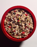Red bowl of multi grain hot cereal with fruit, sunflower and pumpkin seeds.