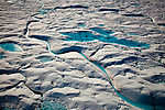 Aerial views of Melt Pools and melt rivers on Petermann Glacier, in remote northwest Greenland. The 80km long, 20km wide floating tongue of Petermann Glacier currently accounts for about 10% of the output of ice from Greenland's Ice Cap. In 2010 and 2012 Petermann calved ice islands totalling 400 square kilometres. (c) 2009 Dave Walsh