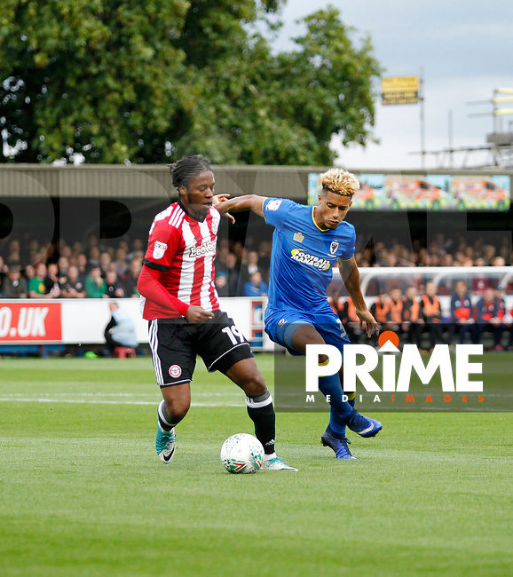 AFC Wimbledon's Lyle Taylor pressures Brentford's Romaine Sawyers during the Carabao Cup match between AFC Wimbledon and Brentford at the Cherry Red Records Stadium, Kingston, England on 8 August 2017. Photo by Carlton Myrie.