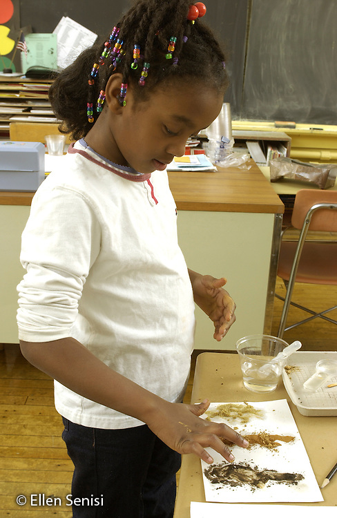 MR / Schenectady, NY.Yates Arts-in-Education Magnet Schl (urban elementary schl) Grade 2 girl (7, Afro-Guyanese) does activity during science lesson. Students observe, experiment with, and record differences in types of soils, their consistency, and water content..Increasingly, hands-on activities are  incorporated into the elementary school science curriculum to motivate students and to improve learning. .MR: AC-g2f Wal7..©Ellen B. Senisi