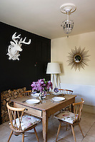 In the intimate dining room the plain wooden table is surrounded by four classic candlestick chairs topped with floral cushions