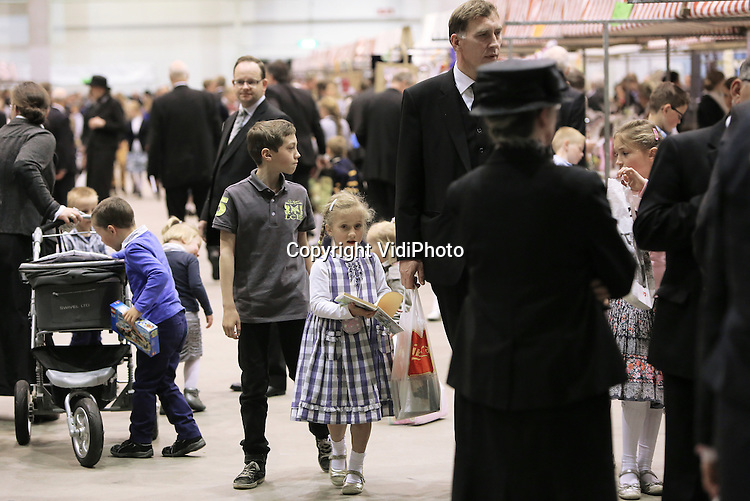 Foto: VidiPhoto<br /> <br /> DEN BOSCH - Een groter contrast is op Koningsdag niet denkbaar. Terwijl miljoenen mensen zich in oranjekleding vrolijk vermaakten op tal van festiviteiten, kwamen enkele duizenden orthodox-gereformeerden zaterdag in de Brabanthallen in Den Bosch bijeen om een andere Koning dan Willem-Alexander -God- te eren: ingetogen en veelal in donkere kleding. Voor de 50e keer werd zaterdag de zogenoemde Mbuma-zendingsdag gehouden. De opbrengst van de bijeenkomst komt ten goede aan zendingswerk in Zimbabwe. Mbuma is een plaatsje in het Afrikaanse land. Bezoekers behoren tot de (Oud) Gereformeerde Gemeenten in Nederland en de rechterflank van de Hersteld Hervormde Kerk.