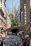 Man wearing a vintage flowered suit jacket and a tall hat with butterflies, sticks, flowers, a birdhouse and a rabbit on top in the Easter Parade on Fifth Avenue in New York City