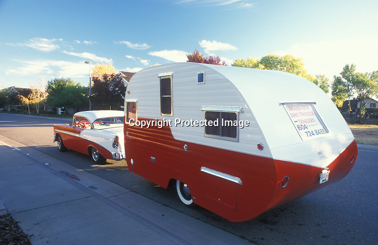 A red and white two-toned 1956 Chevrolet pulling a two-toned red and white retro canned ham vintage trailer.
