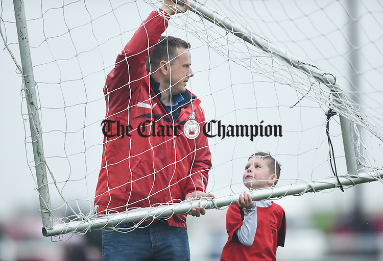 Alan Mc Auley gets some help removing the goals from Luke Deegan following the childrens  half time game  during the Cup final at Doora. Photograph by John Kelly.