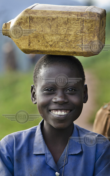 A school girl carrying an empty water container on her head in the Mabayi Commune, Ruhororo Colline.