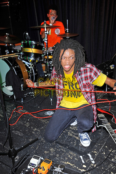 Solomon Radke &amp; Dee Radke of Radkey <br /> performing in concert, The Blackeart, Camden, London, England. <br /> 17th October 2013<br /> on stage in concert live gig performance performing music full length red check shirt yellow top kneeling drums<br /> CAP/MAR<br /> &copy; Martin Harris/Capital Pictures