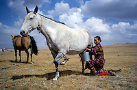 A Kyrgyz woman collecting milk from a female horse..The M41 Highway from the Ismaili capital of Khorog to the south capital of Kyrgyzstan - Osh, via the head district of Badakhshan - Murgab and the Akbajtal Pass at 4655 meters.