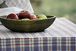 Civil War period table with a fruit bowl full of apples.  Flies on table cloth