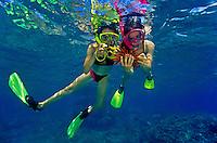 Two girls snorkeling at Hanauma Bay examine pencil slate sea urchin